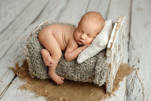 sesja-starszy noworodek-w łóżeczku